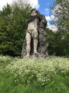 Giant stone Statue of Neptune in a green garden, with blue sky