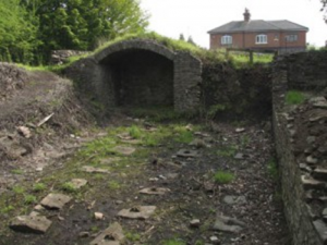 Archaeological remains in the ground and a stone built archway
