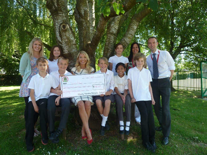 Alex Lovell holding a large cheque with pupils form the school